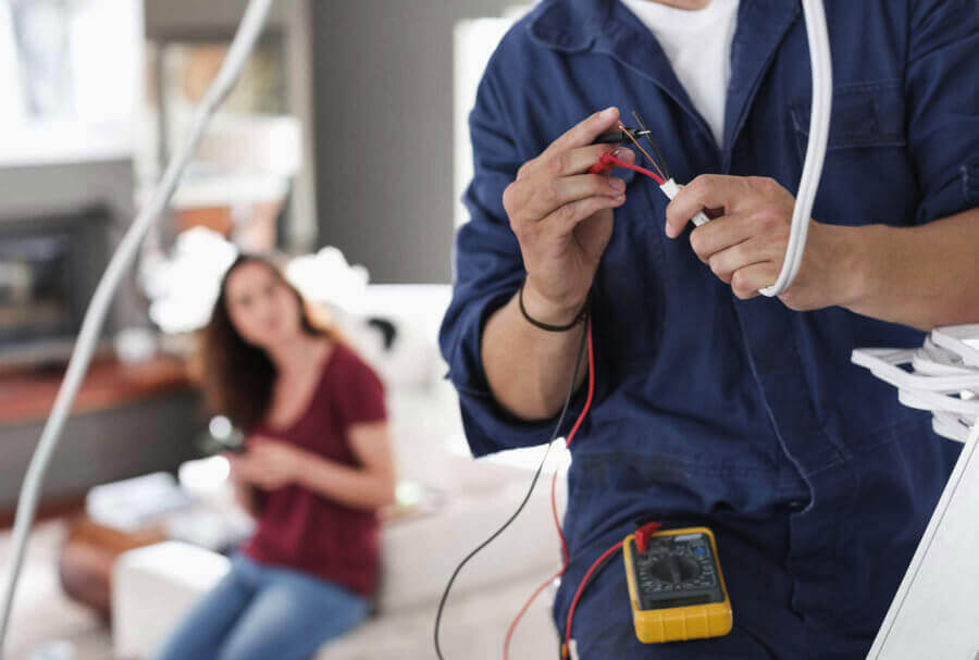 Electrician rewiring a home while being watched by home owner