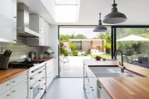 Modern fitted kitchen extension with roof lights and large sliding doors