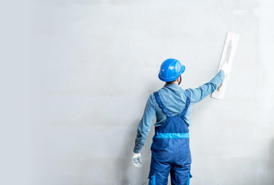 Tradesman plastering large wall smoothing with float Glasgow