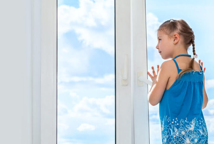 Small girl looking out of a set of double glazed windows in Glasgow