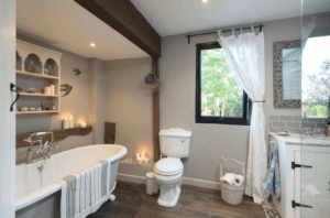 Old bathroom style with exposed wooden beams and roll top bath