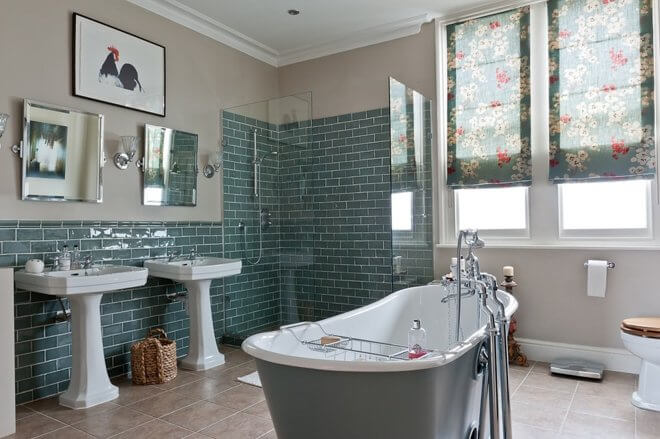 Elegant green subway tiled bathroom with stylish roll top bath