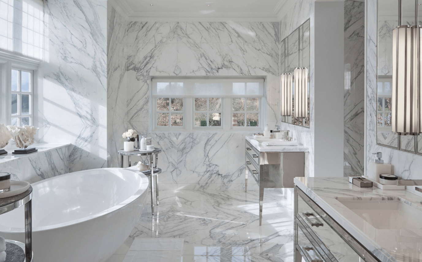 Marble walled sophisticated bathroom with stylish oval ceramic bath