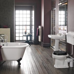 Maroon coloured bathroom with victorian styled bathroom suite and taps