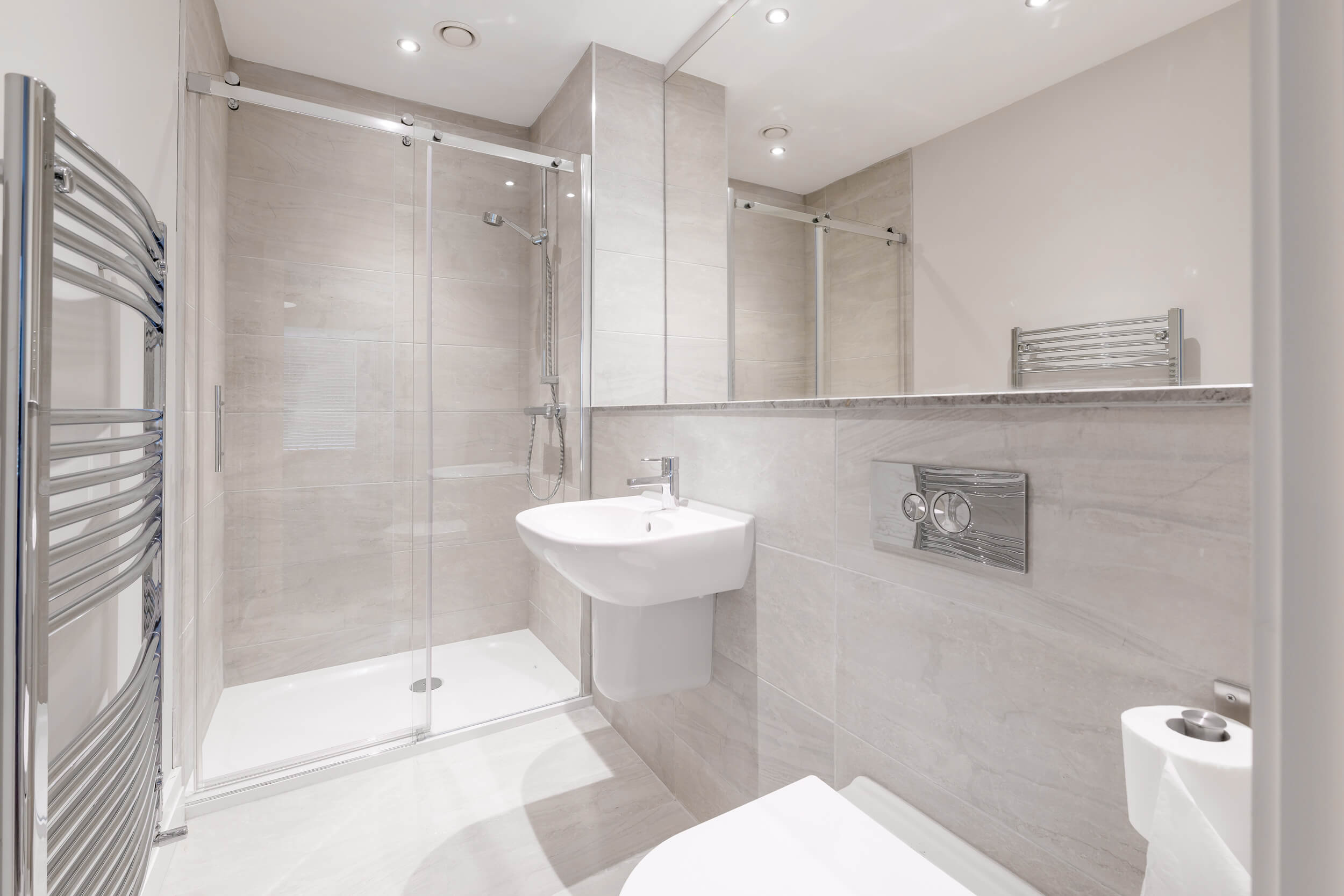 Fitted bathroom with enclosed shower, designer radiator and modern bathroom suite